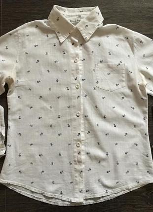 Белая рубашка с изображением скелета рыб и бантиков.